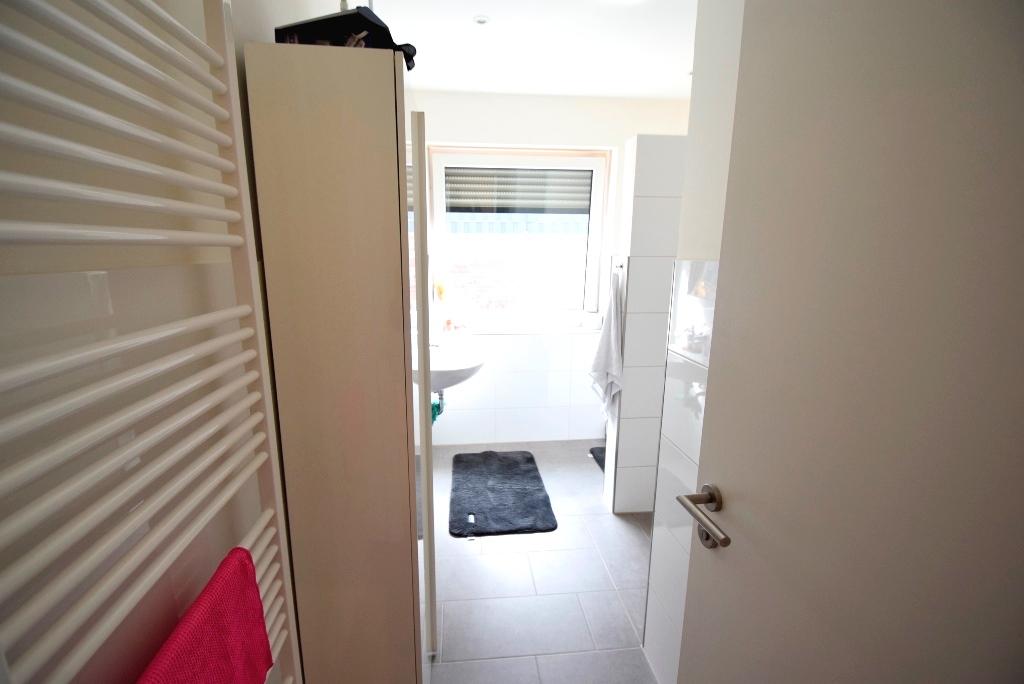 Blick ins Bad mit ebenerdiger Dusche, Fenster und Handtuchheizkörper
