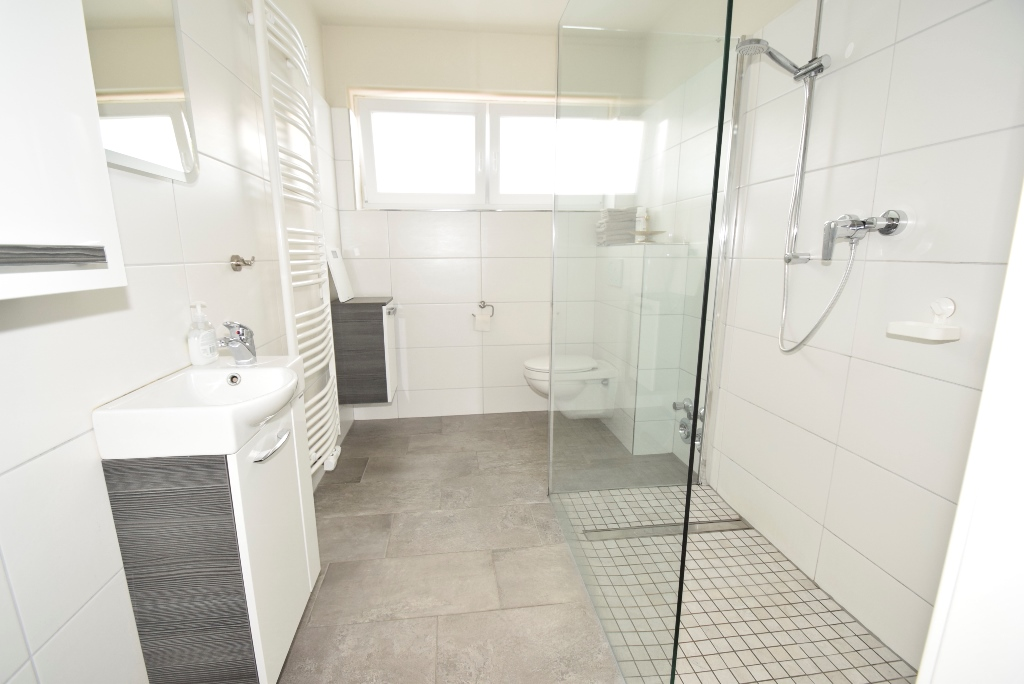 Helles Badezimmer mit ebenerdiger Dusche und Handtuchheizkörper